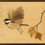 Photo of wood art depicting chichadee and maple twig with leaves