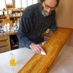 Photo of Gary Wood applying finish to a board