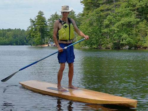 Photo of man paddling SUP on a lake