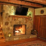 Photo of stone fireplace with live edge curly maple mantle