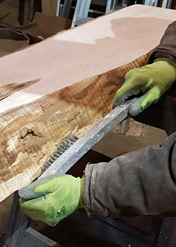 Photo of cleaning the edge of a live edge slab with a wire bristled brush