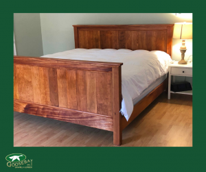 Photo of bed with table and lamp. Photo is branded to Goosebay Lumber and Sawmill